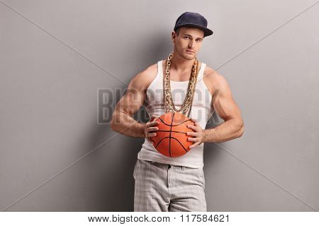 Young man with gold chain holding a basketball and looking at the camera