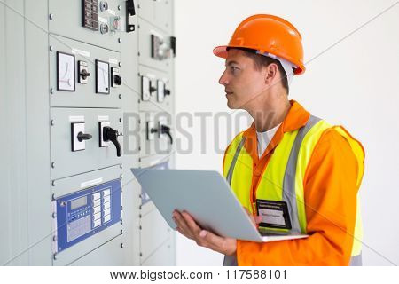 electrical engineer with laptop computer in power plant control room