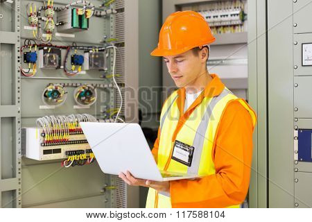experienced industrial engineer using laptop computer in machine control room