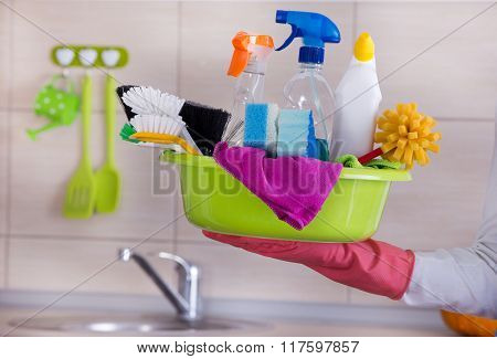 House Cleaner Carring Cleaning Supplies In One Hand