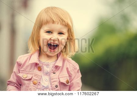 Beautiful laughing 2 year old girl in the street close up
