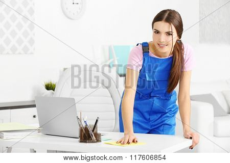 A pretty young woman in uniform wiping furniture at the office