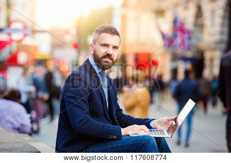 Hipster manager working on laptop on sunny Piccadilly Circus, Lo