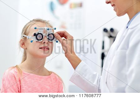 health care, medicine, people, eyesight and technology concept - optometrist with trial frame checking girl patient vision at eye clinic or optics store