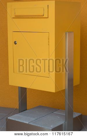 Yellow Post Box Stands On Concrete Base