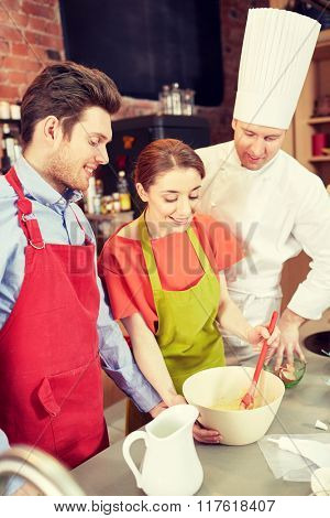 cooking class, bakery, cooking food and people concept - happy couple and male chef cook prepearing cream or dough in kitchen
