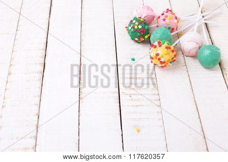 Colorful Cake Pops On White  Painted Wooden Background.