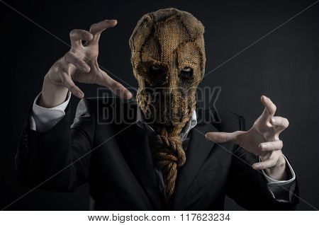 Fear And Halloween Theme: A Brutal Killer In A Mask On A Dark Background In The Studio