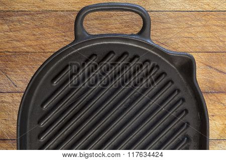 Black grill pan on wood background