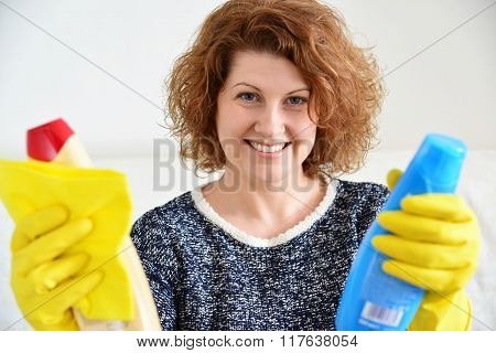 happy woman in rubber gloves with a cleaning agents