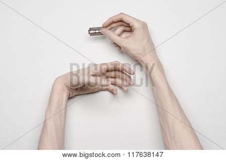Suicide and Halloween theme: the human hand holding the blade to suicide isolated on white background top view poster
