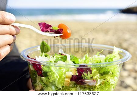 closeup of a young caucasian man eating a prepared salad next to the sea