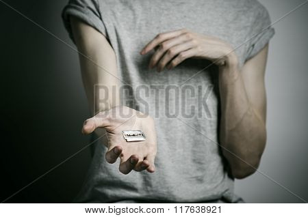 Depression and suicide theme: man holding a razor to suicide on a gray background poster