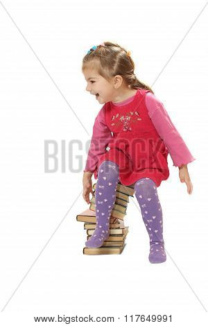 The Little Girl Sitting On A Pile Of Books