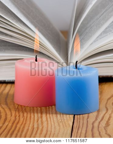 two candles on open book background