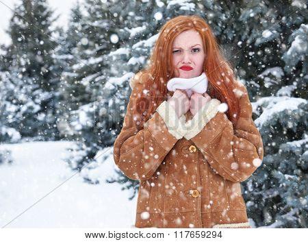 Grimacing woman having discomfort on winter weather, outdoor portrait