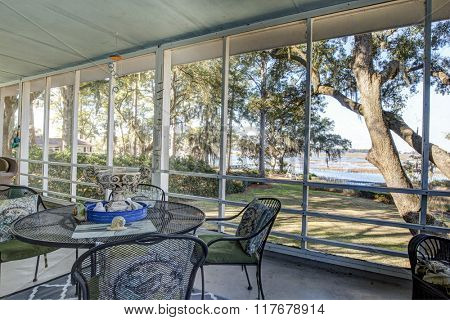 Screen porch with view of trees and waterfront