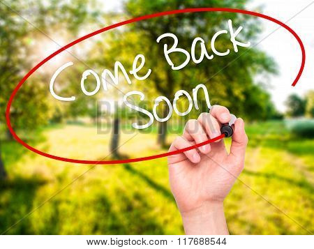 Man Hand Writing Come Back Soon With Black Marker On Visual Screen.