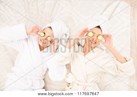 Two Girls  With Cucumbers On Eyes  Lying On The Bed