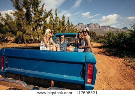 Group Of Friends Sitting At The Back Of A Pick Up Car