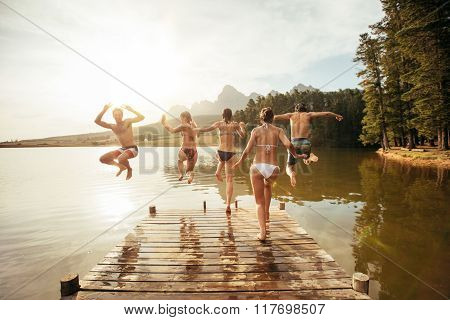 Young Friends Jumping Into A Lake