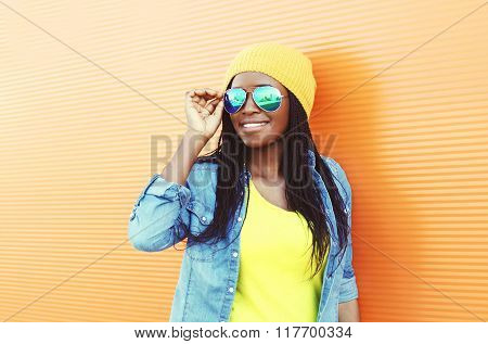 Beautiful Smiling Young African Woman Wearing A Sunglasses Over Orange Background