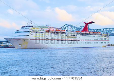 February 1, 2016 in New Orleans, LA:  Carnival Cruise Ship Elation where tourists can enjoy a relaxing cruise to the Yucatan of Mexico departing southbound on the Mississippi River with the Crescent City Connection Bridge beyond taken in New Orleans, LA
