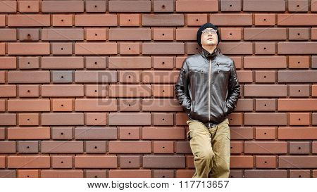 An Asian Man in a Brown Jacket Leans Against the Wall