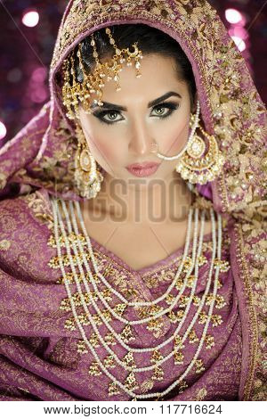 Portrait of a beautiful female fashion model in ethnic asian indian bridal costume with heavy jewellery and makeup poster