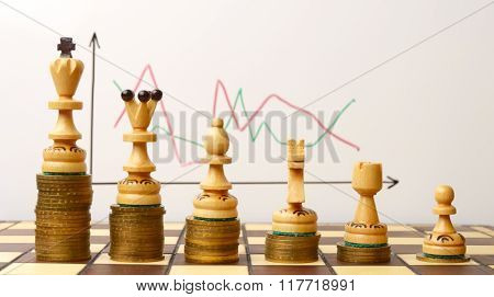 White chess pieces on the pile of coins