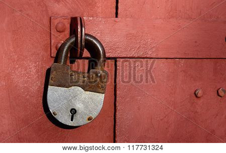 Closeup Of Old Lock On Red Metal Garage Door