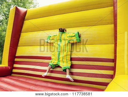 Young Woman In Plastic Dress In A Bouncy Castle Imitates A Fly On Velcro Wall, Inflatable Attraction