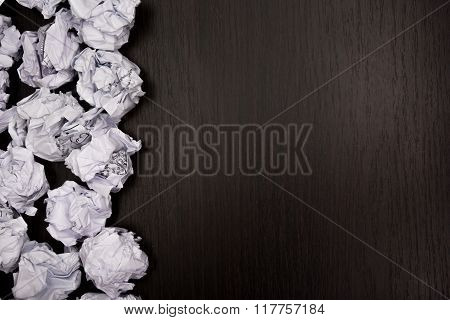 Crumpled paper balls and blank sheet of paper with pencil on black background. Paper wad. Creativity