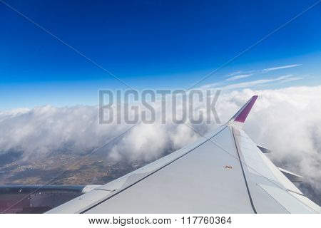 Blue horizon and white clouds. Aerial shot with airplane wing