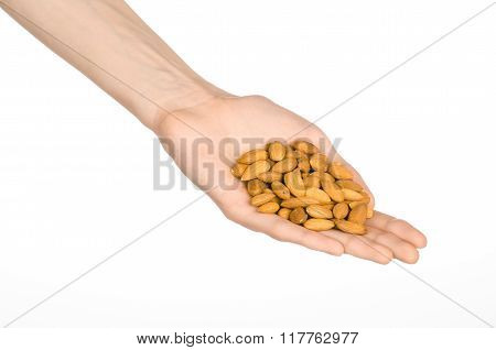 Nuts And Cooking Theme: Man's Hand Holds Nuts Almonds On A White Isolated Background In Studio