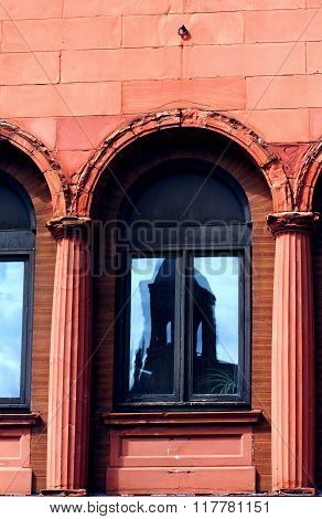 Historic Douglass Hotel reflects in the window of a rundown building in Houghton Michigan. Arches over window are broken and deteriorating. Building is constructed of redsandstone blocks.