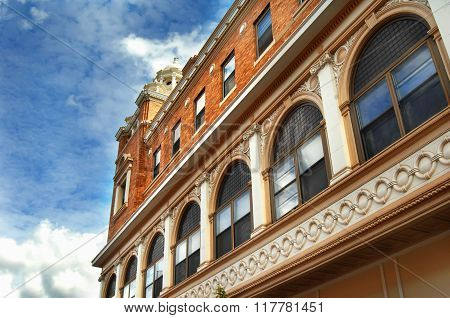 Low angle shot of the historic Douglass Hotel in Houghton Michigan. Row of arched windows line the front of the hotel and a glimpse of the domed top can just be seen.