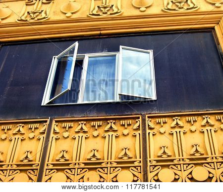 Very unusual window framing catches the eye with its bright yellow paint and intricately carved design. Window is open and catches the reflection of a blue sky.