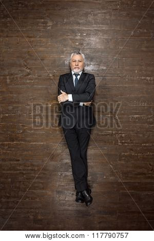 Top view creative photo of senior businessman on vintage brown wooden floor. Businessman looking at camera with arms crossed