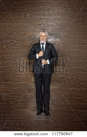 Top view creative photo of senior businessman on vintage brown wooden floor. Businessman looking at camera and straightening suit