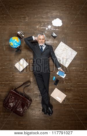 Top view creative photo of senior businessman on vintage brown wooden floor. Businessman lying with blank white cloud and holding passport with tickets. There are travel objects near him