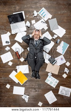 Top view creative photo of senior businessman on vintage brown wooden floor. Angered and tired businessman lying on office objects. There are documents on floor