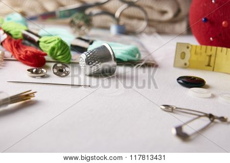 Composition tools for embroidery on white fabric. Horizontal composition. Front elevated view poster