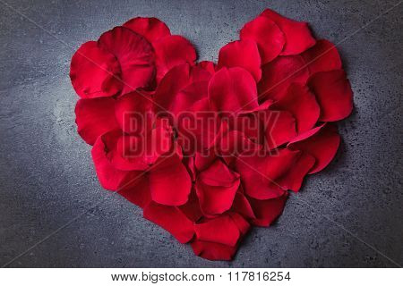 Heart made of rose petals on wooden background