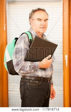 Older Man Representing Lifelong Learning. Man With School Bag Smiling As A Gesture Of Happiness And