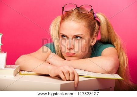 Angry, Bored Schoolgirl With Two Hair Tails And Big Eyeglasses Leaning On Small Table Full Of Books