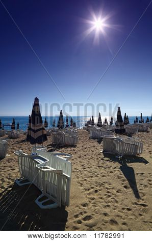 Empty Sandy Beach With Folded Umbrellas And Sunbeds, Burning Sun And Cloudless Sky