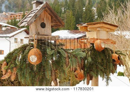 Two wooden bird feeders decorated with pine tree branches with coconut shell suet treats hanging