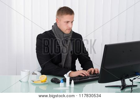 Sick Businessman Using Computer In Office