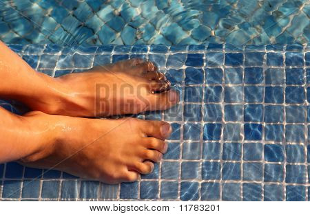 Small Boy Feet Are Jointed And Putted In Water Of Blue Swimming-pool